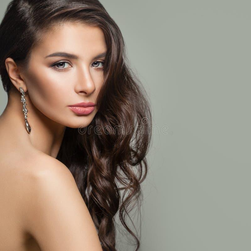 有长的波浪发型、构成和金刚石首饰耳环的完善的妇女 免版税库存图片