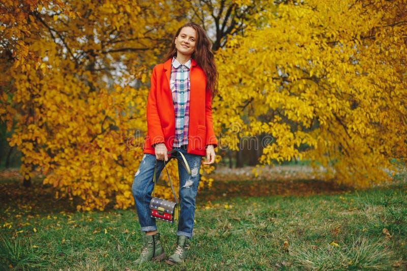 有长的波浪发的女孩享受秋天的在公园 免版税库存照片