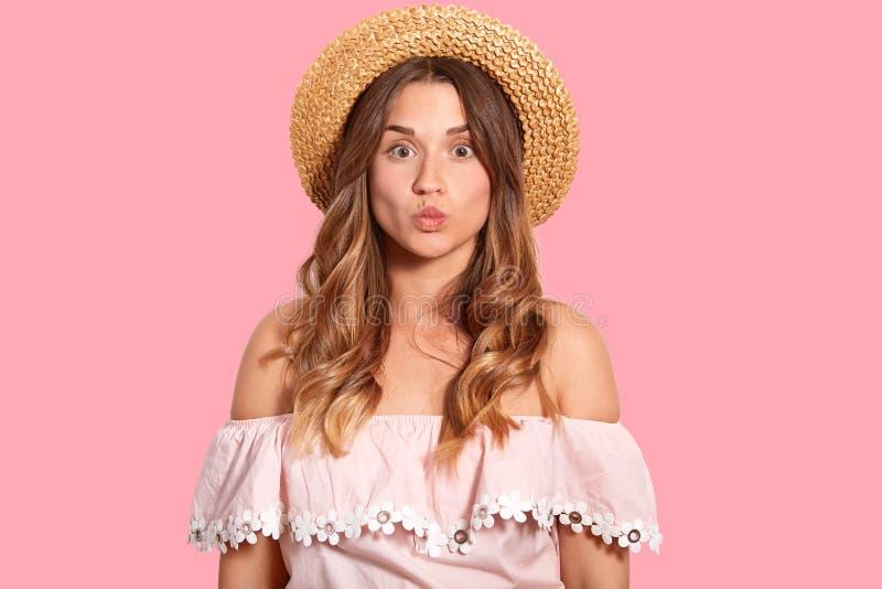 有长的波浪发的美丽的欧洲妇女,噘嘴嘴唇,做鬼脸,穿草帽,并且夏天女衬衫,有健康皮肤, 免版税库存照片