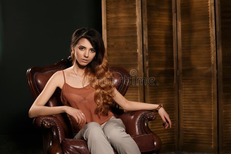 有长的波浪发稀薄的苗条形象的完善的身体和俏丽的面孔美丽的性感的年轻深色的妇女化妆佩带米黄e 免版税库存图片