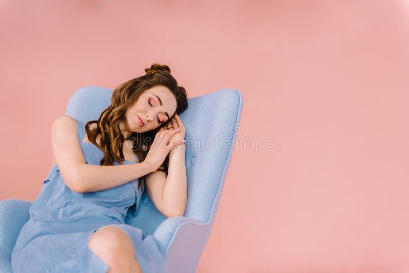 有长的流动的头发和一件蓝色礼服的一个女孩,睡着了在a 免版税库存照片