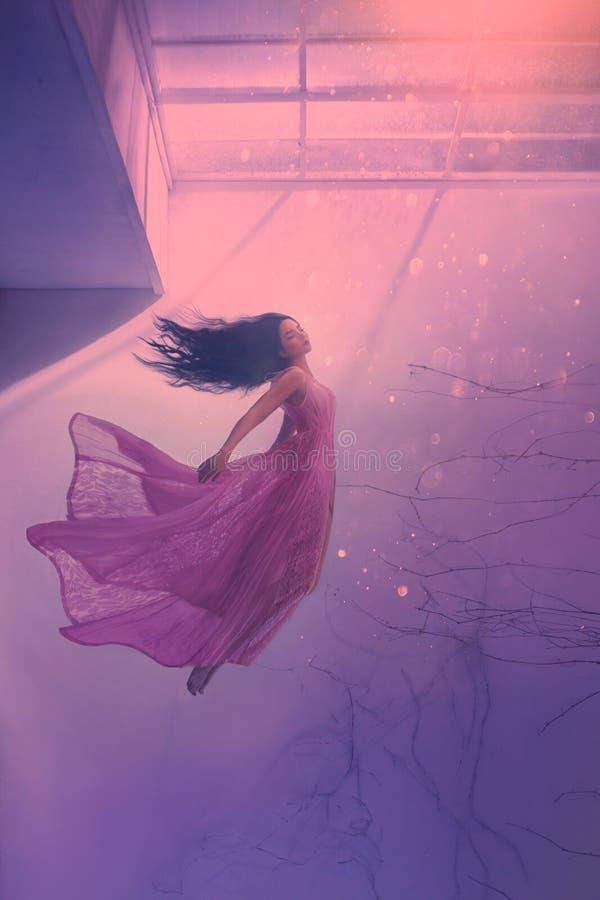 有长的流动的黑色头发的,在长的飞行的桃红色招标礼服,下沉的夫人的浮动的秀丽神奇睡觉的女孩 图库摄影
