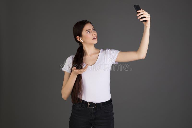 有长的深色的头发的严肃的女实业家在白色T恤 库存图片