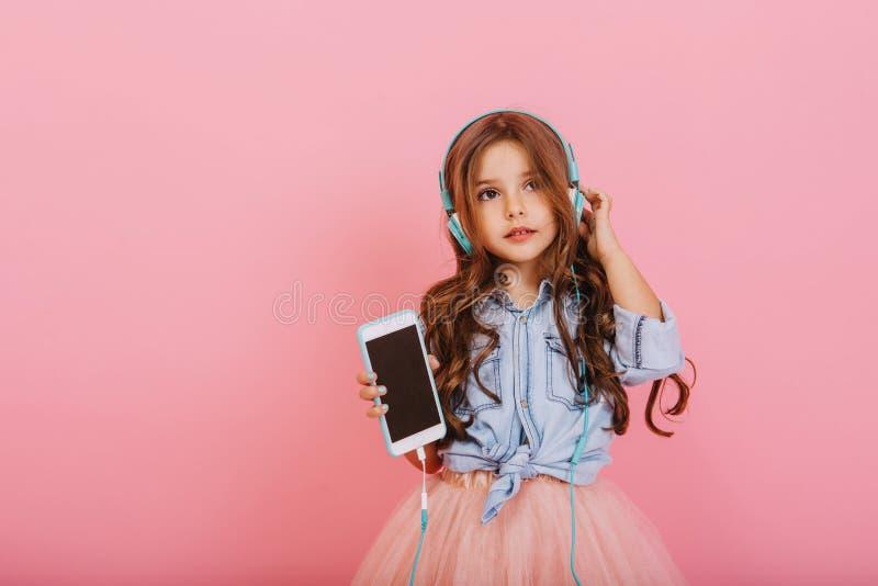 有长的深色的头发的美丽的女孩有电话的听到音乐的通过在桃红色隔绝的蓝色耳机 图库摄影