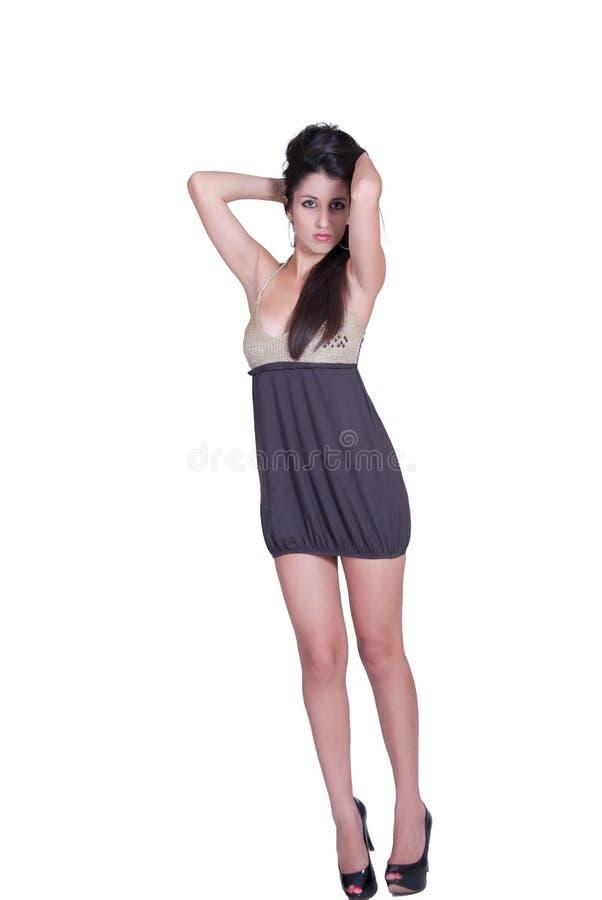 有长的深色的头发穿戴短小领口礼服和黑高跟鞋的时尚妇女 免版税库存照片