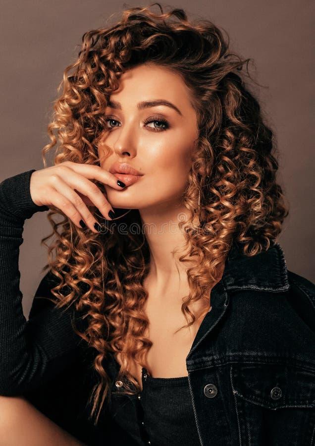 有长的白肤金发的卷发的美女在典雅的衣裳 图库摄影
