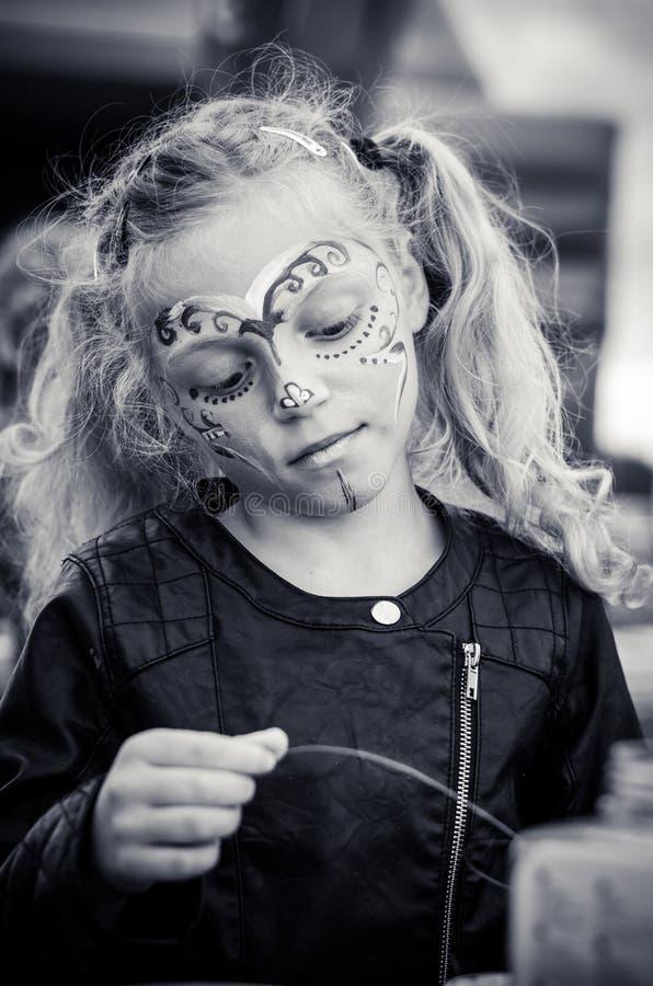 有长的白肤金发的被盯梢的头发和面孔绘画的小女孩 免版税库存照片