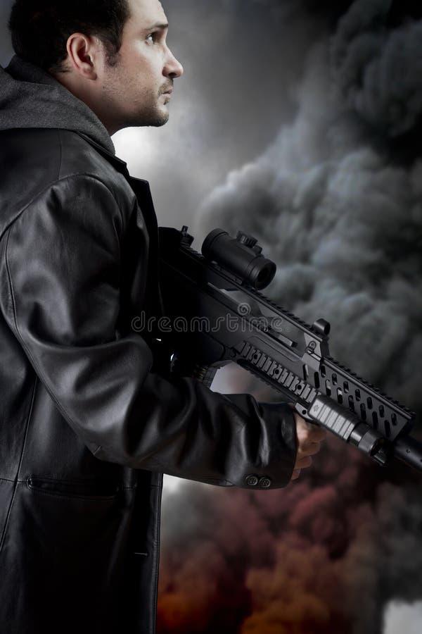 有长的皮夹克和攻击步枪的人 免版税图库摄影