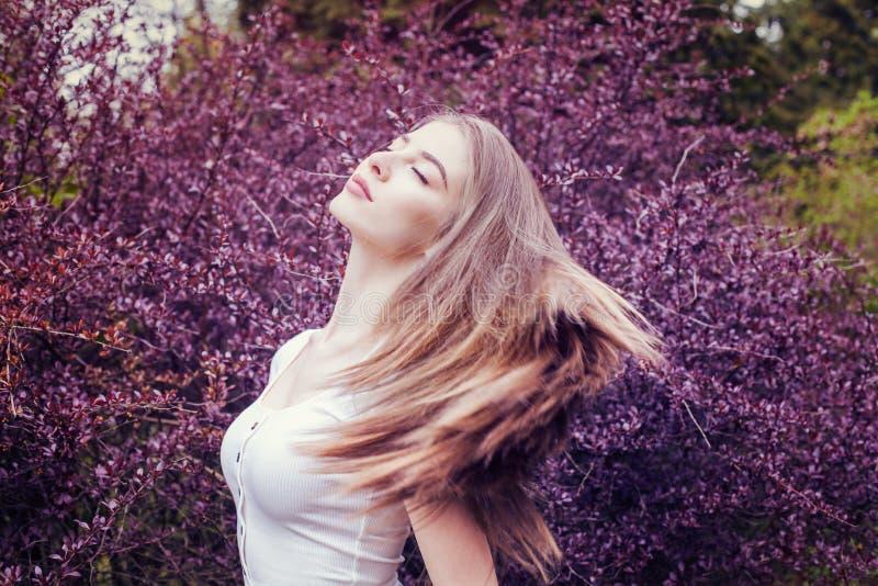 有长的直发画象的俏丽的年轻女人反对紫色花背景 免版税库存照片