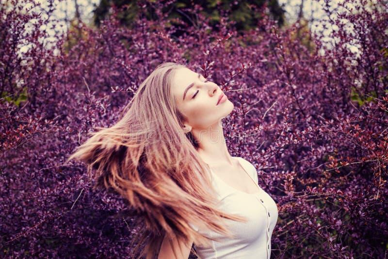 有长的直发的年轻女人在花背景 免版税图库摄影
