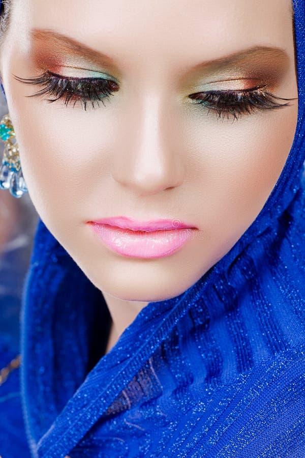有长的睫毛的妇女在蓝色 免版税库存图片