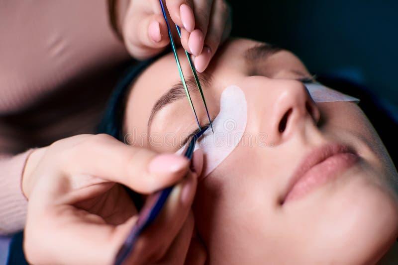 有长的睫毛的美丽的妇女在美容院 睫毛引伸做法 鞭子关闭  免版税库存照片
