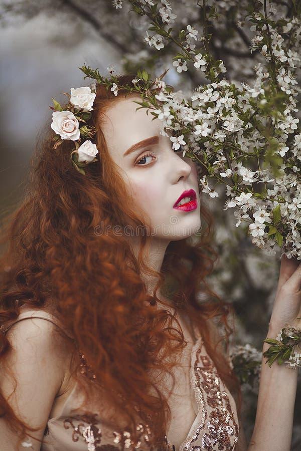有长的红色头发的一名柔和的妇女在一个开花的春天庭院里 有苍白皮肤和蓝眼睛的红色肉欲的女孩与明亮 免版税库存图片