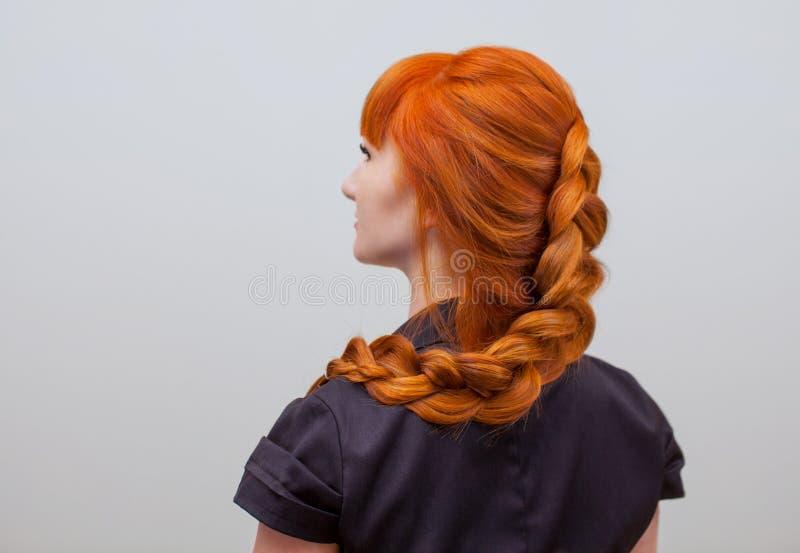 有长的红色头发的美丽的女孩,编辫子与法国辫子,在美容院 免版税库存照片