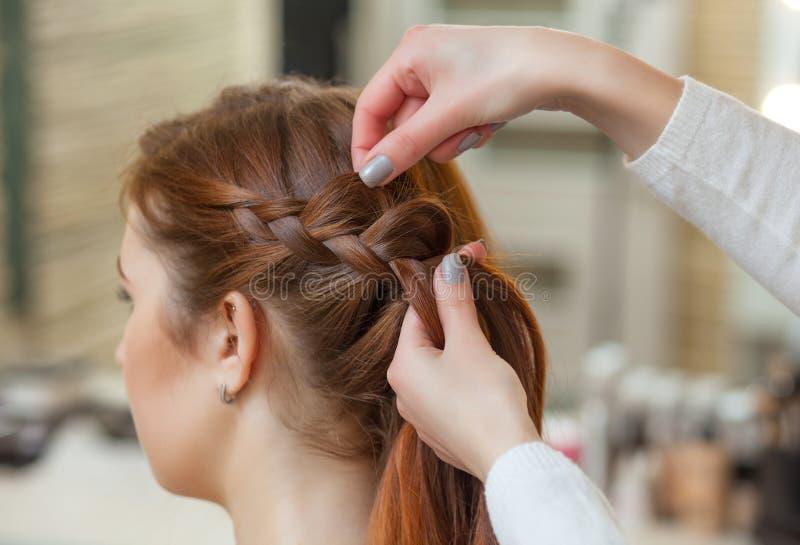有长的红色头发的美丽的女孩,美发师编织一条辫子,在美容院 免版税图库摄影