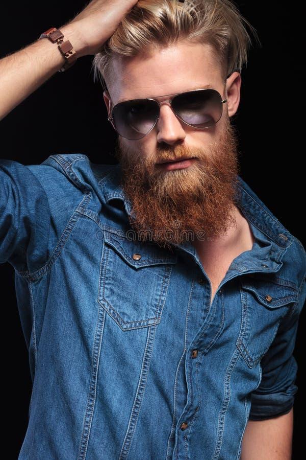 有长的红色胡子佩带的太阳镜的人,修理他的头发 库存图片