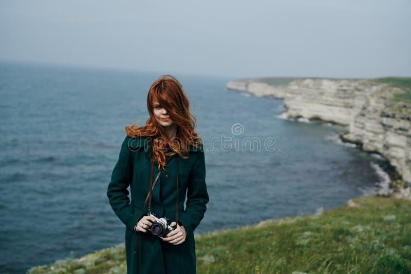 有长的红色头发的美丽的妇女拿着照相机在山边缘在海附近 免版税库存照片