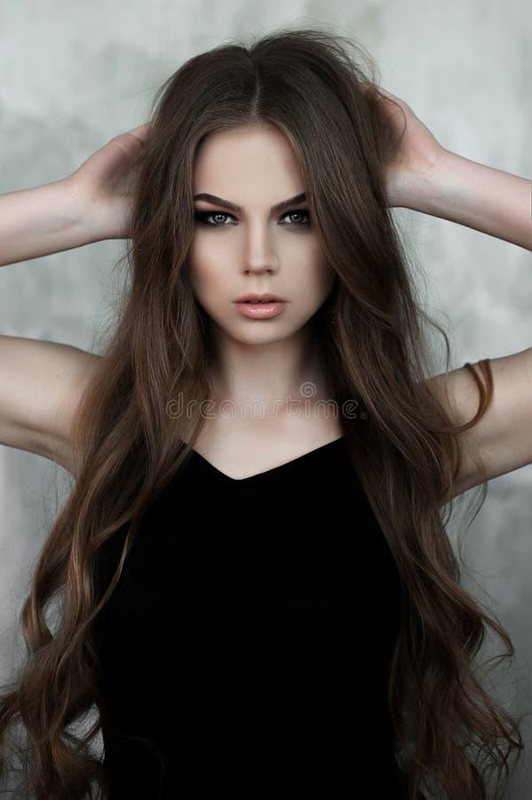 有长的美丽的穿黑最大的晚礼服的头发和发烟性眼睛的女孩 美丽的夫妇跳舞射击工作室妇女年轻人 库存照片