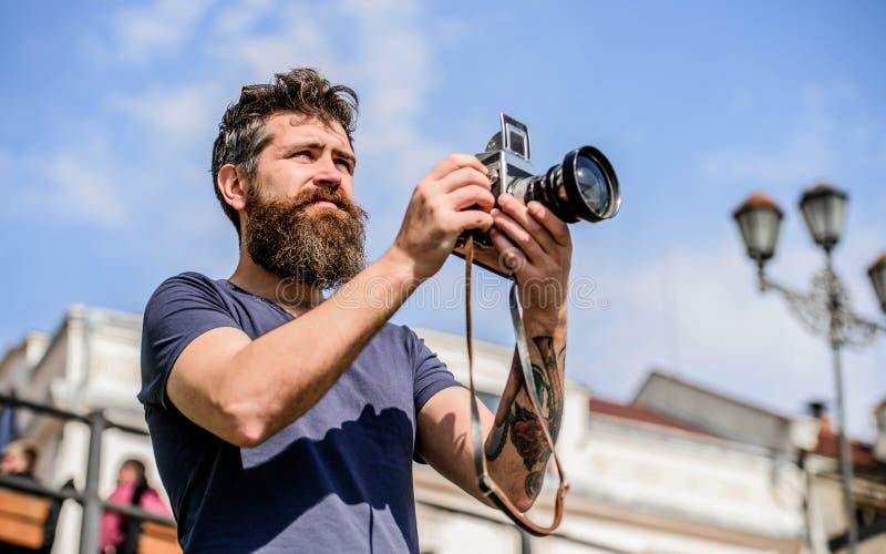 有长的胡子射击照片的人 手工设置 摄影师举行葡萄酒照相机 现代博客作者 美满的创作者 免版税库存照片