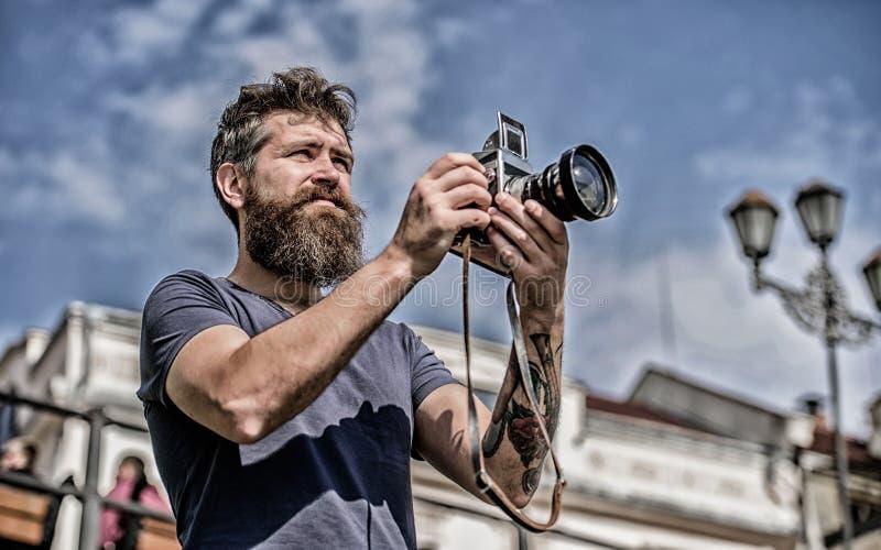 有长的胡子射击照片的人 手工设置 摄影师举行葡萄酒照相机 现代博客作者 美满的创作者 库存照片