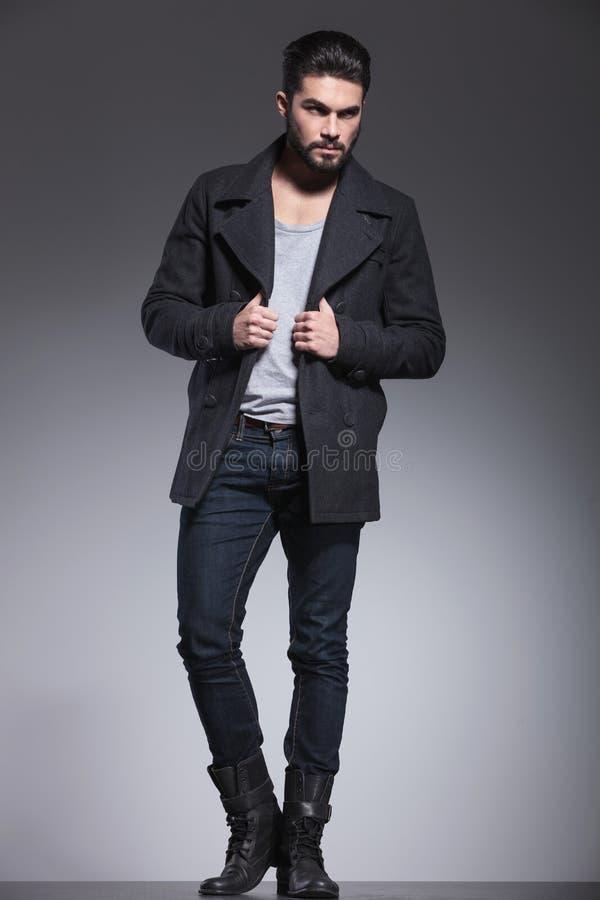 有长的胡子的年轻人拿着他的外套的衣领 免版税库存照片
