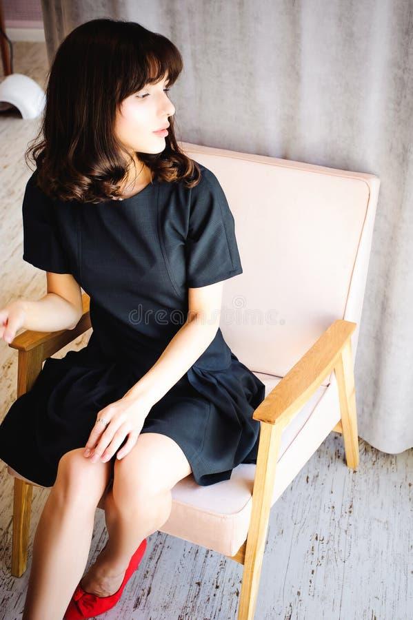 有长的腿的年轻可爱的妇女在黑庄重装束,在椅子坐在室内部的窗口附近  库存照片