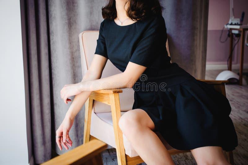 有长的腿的年轻可爱的妇女在黑庄重装束,在椅子坐在室内部的窗口附近  免版税库存照片