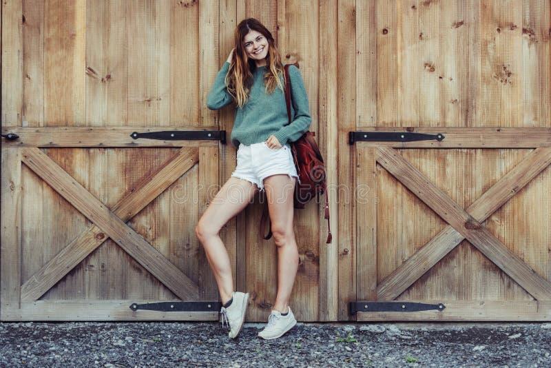 有长的腿的愉快的妇女看到穿有短裤、背包和运动鞋的农场的旁边近的谷仓偶然服装 库存照片