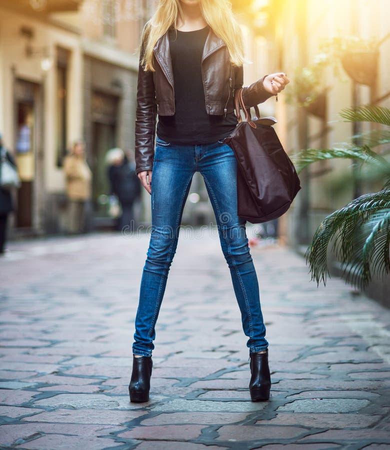 有长的腿的时兴的年轻白肤金发的女孩穿蓝色牛仔裤,皮革棕色外套和拿着袋子走和购物在城市的 库存图片