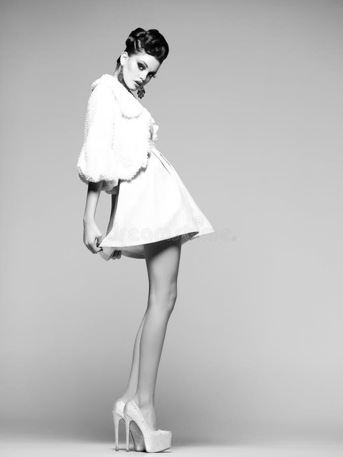 有长的腿的美丽的妇女在白色礼服、摆在演播室的毛皮和高脚跟 免版税图库摄影