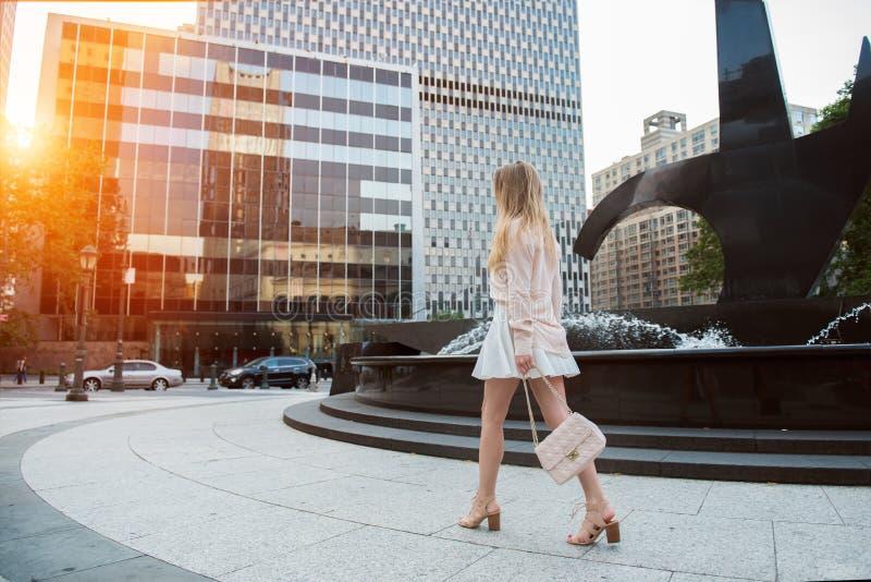 有长的腿的美丽的少妇走在城市街道上的穿短裙和桃红色T恤杉和拿着袋子 免版税库存图片