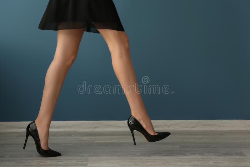 有长的腿的美丽的年轻女人走对颜色墙壁的 图库摄影