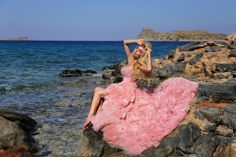 有长的腿的美丽的白肤金发的妇女在一件桃红色舞会礼服 免版税库存照片