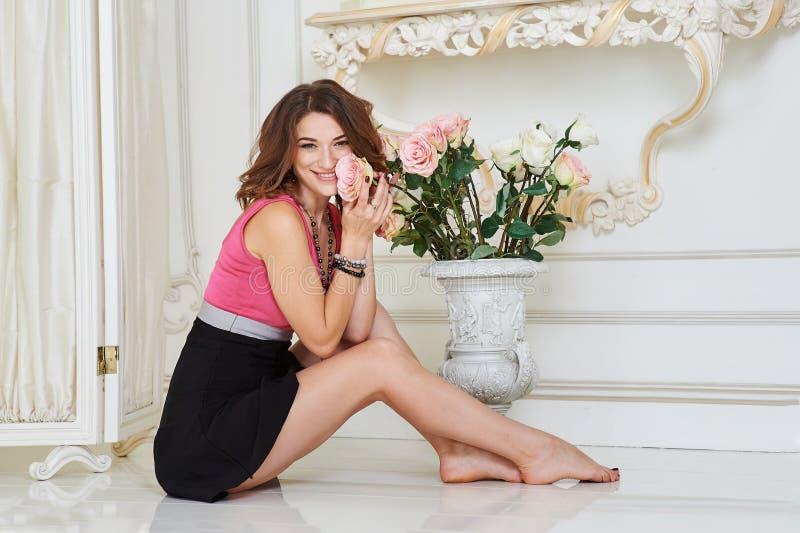 有长的腿的年轻美丽的妇女坐在内部的地板 免版税图库摄影