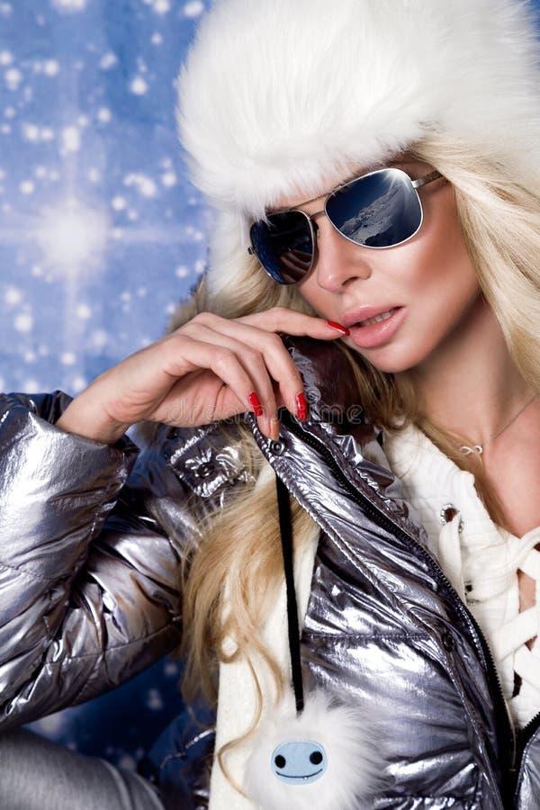 有长的金发和完善的面孔的美丽的惊人的妇女在冬天衣物、银温暖的夹克和毛皮盖帽穿戴了 免版税库存照片