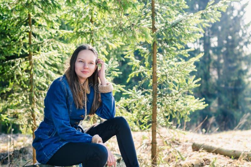 有长的金发和牛仔布夹克的一少女坐日志并且调直她的头发在温暖的一个绿色具球果森林里 图库摄影
