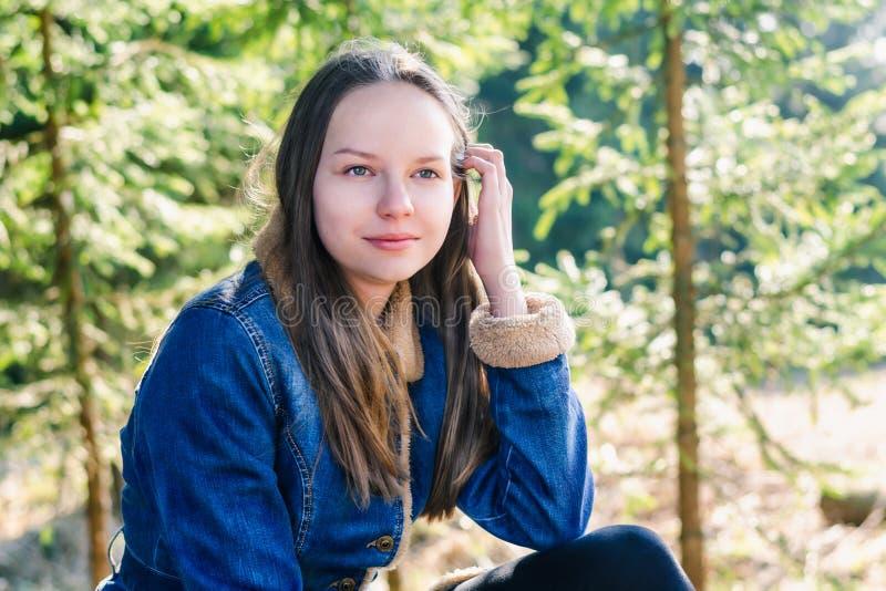 有长的金发和牛仔布夹克的一美丽的少女在一个绿色具球果森林里调直她的头发 库存图片