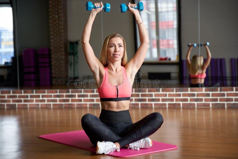 有长的金发的亭亭玉立的少妇有强烈的表示的提起哑铃,当坐在健身房时的体育席子 库存图片