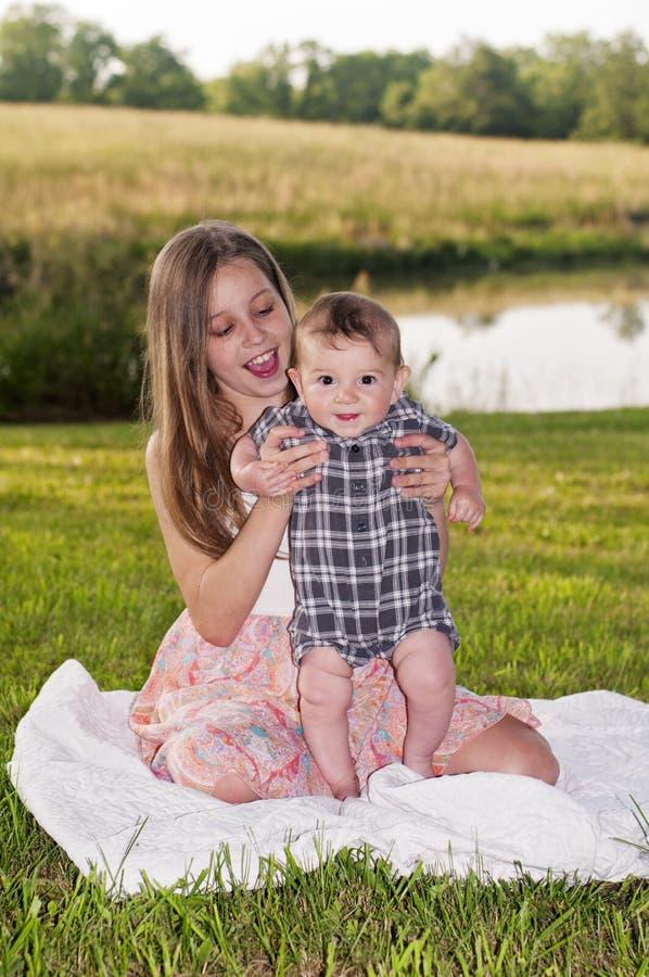 有长的金发的俏丽的女孩坐有愉快的男婴的一条毯子 免版税库存图片