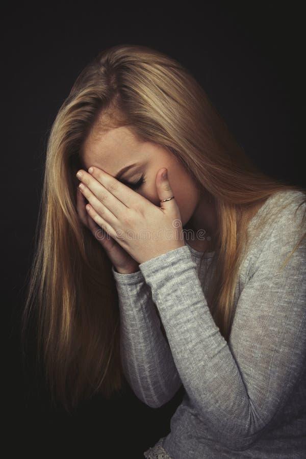 有长的金发的十几岁的女孩哭泣用她的手的由她的面孔决定 免版税库存图片