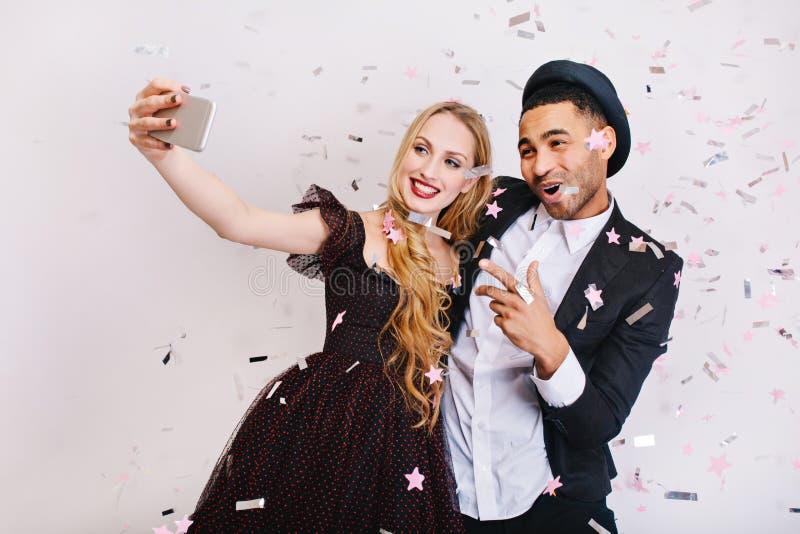 有长的金发的可爱的年轻女人在做在闪亮金属片的豪华晚礼服selfie与快乐的帅哥 免版税图库摄影