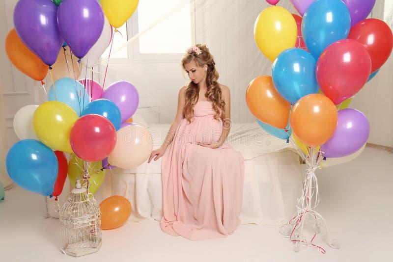 有长的金发的孕妇在庄重装束,与很多五颜六色的气球 免版税图库摄影