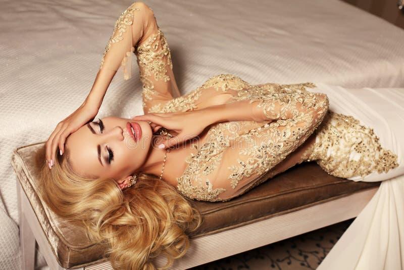 有长的金发的性感的妇女佩带luxurios鞋带婚礼礼服和珠宝 免版税库存图片