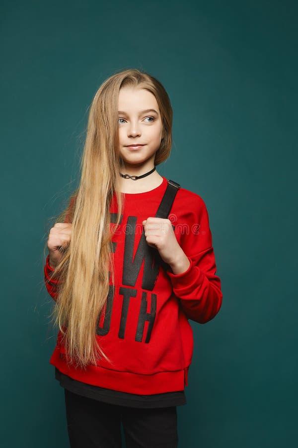有长的金发的时髦的青少年,美丽的年轻式样女孩,摆在牛仔裤和红色运动衫的演播室 免版税图库摄影