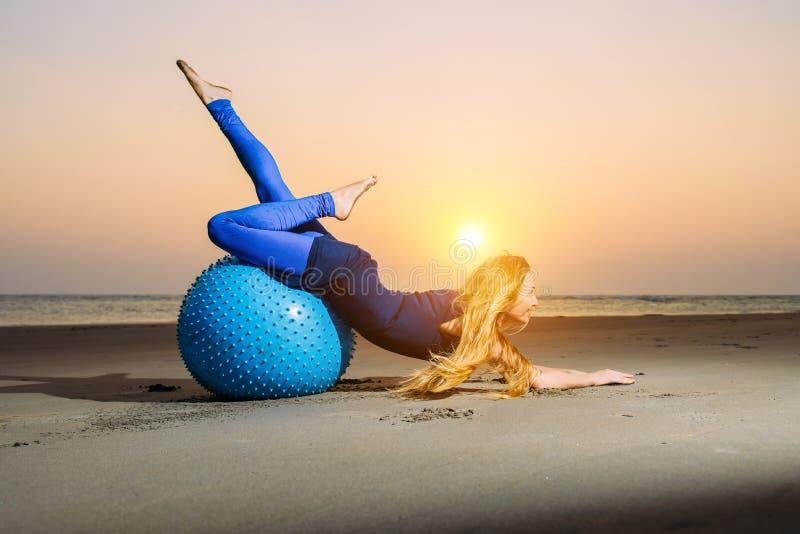 有长的金发的灵活的少女行使在瑜伽球的 体操运动员妇女和大体育球在平衡的光 免版税库存图片
