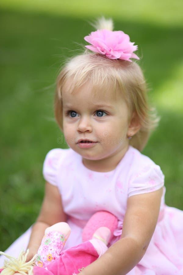 有长的金发的甜点微笑的小女孩,坐草在夏天公园,特写镜头室外画象 免版税库存照片