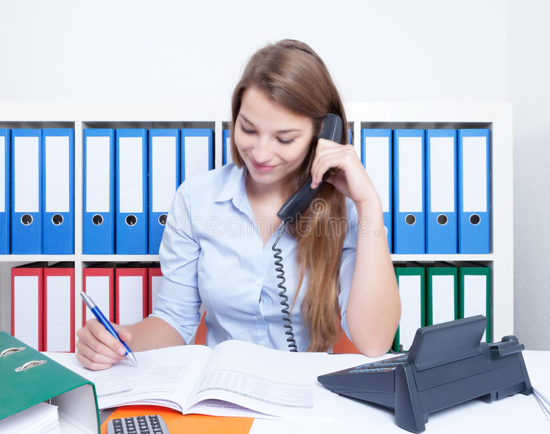 有长的金发的美丽的妇女在办公室谈话在电话 库存照片