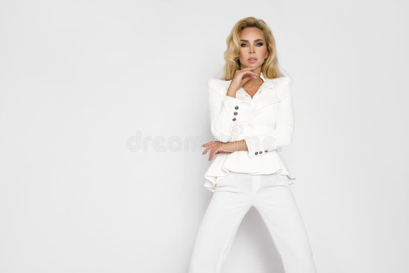 有长的金发的美丽的妇女,穿戴在典雅,白色春天穿衣 免版税库存图片