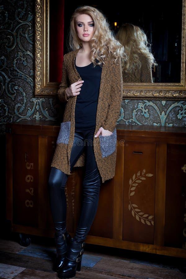 有长的金发的美丽的年轻性感的妇女,明亮的构成Smokey注视佩带毛线衣在梳妆台旁边和与a.c.的一个酒吧 免版税库存图片