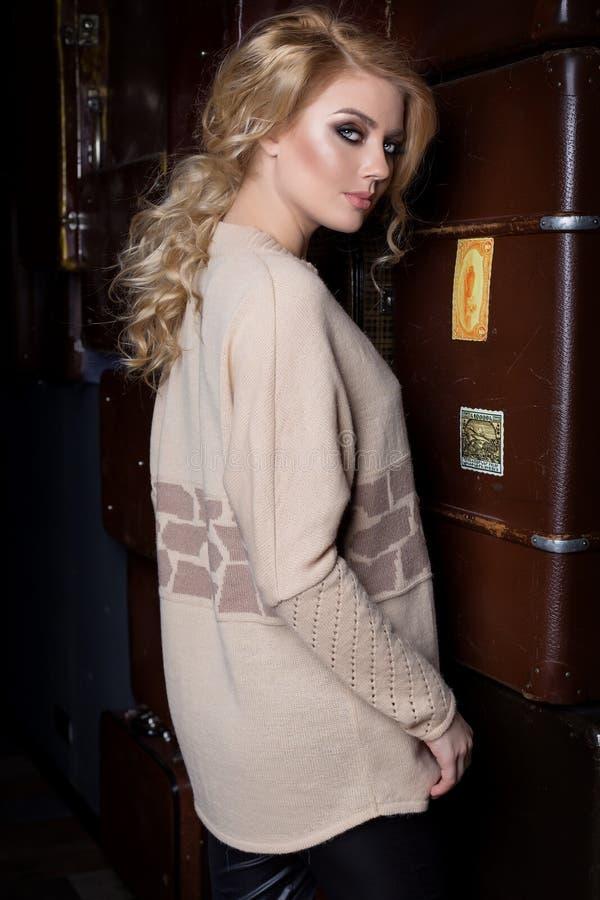 有长的金发的美丽的年轻性感的妇女,明亮的构成Smokey注视佩带毛线衣在梳妆台旁边和与a.c.的一个酒吧 库存照片